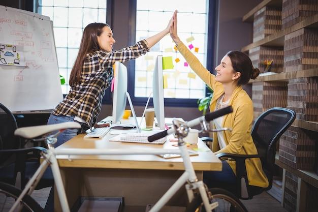 Collègues féminines high fiving au bureau d'ordinateur