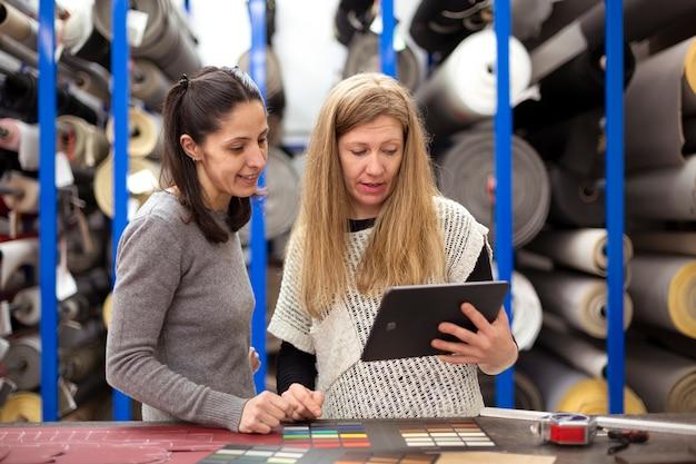 Des collègues féminines regardent quelque chose sur une tablette numérique