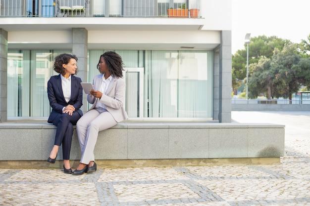 Collègues féminines avec tablette en plein air