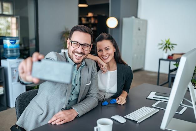 Des collègues féminins et masculins prenant selfie au bureau.