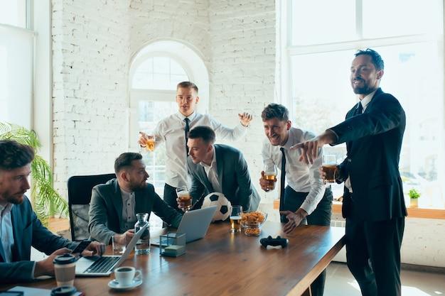 Des collègues heureux s'amusant au bureau pendant que leurs collègues travaillent dur
