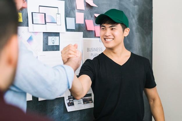 Collègues heureux se tenant la main au bureau