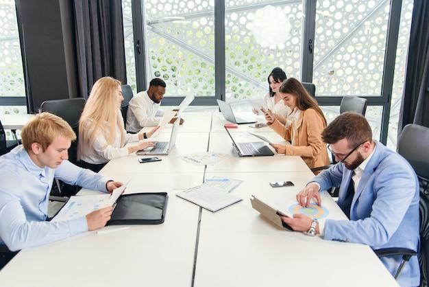 Des collègues internationaux étudient différents documents commerciaux et travaillent avec des ordinateurs portables et des tablettes dans le centre de bureau moderne.