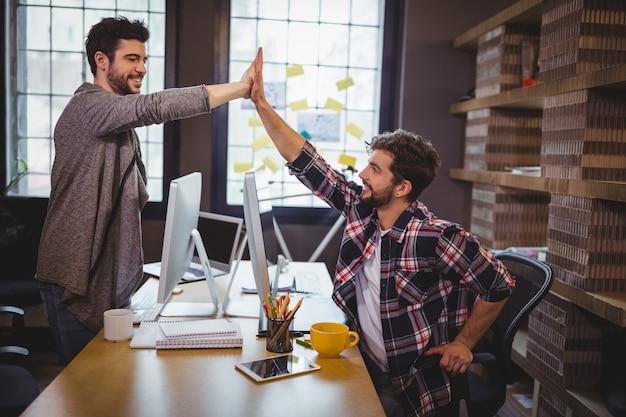 Collègues masculins fiving élevé au bureau