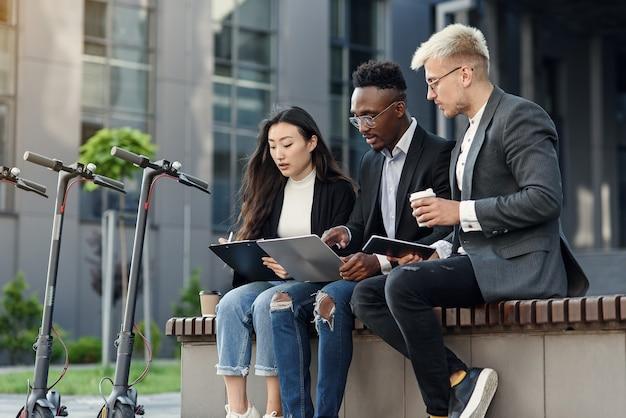 Collègues multiraciales élégants assis sur le banc près du bureau et discutant des affaires
