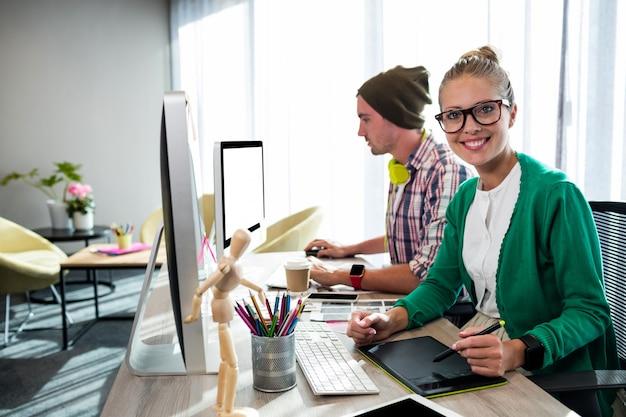Collègues occasionnels à l'aide d'une tablette graphique et d'un ordinateur
