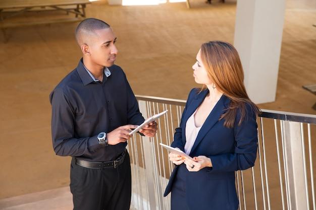 Collègues parlant et tenant des tablettes dans les escaliers