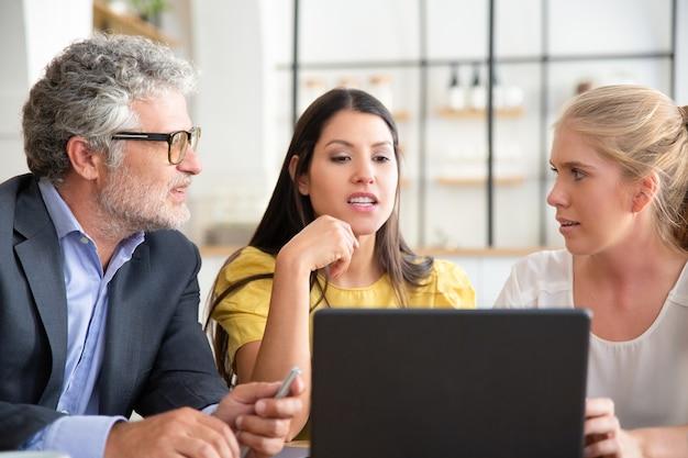 Collègues ou partenaires d'affaires regardant du contenu sur un ordinateur portable et discutant du projet