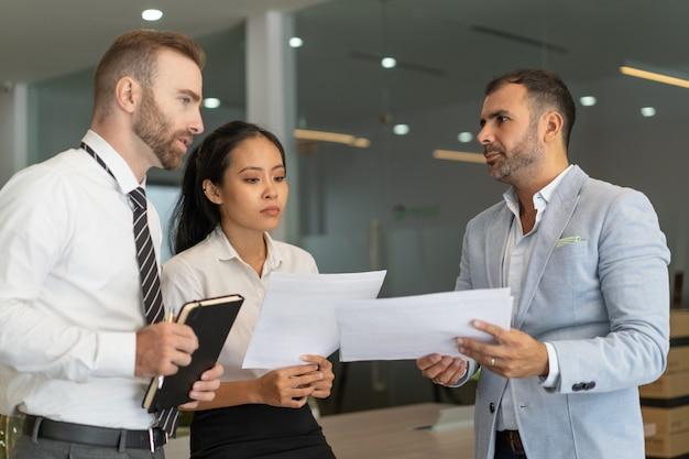 Des collègues pensifs visionnant des papiers d'affaires au bureau