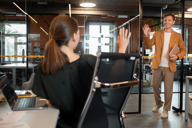 Collègues de plan moyen agitant la main les uns aux autres