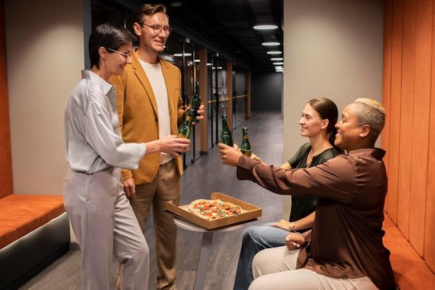 Collègues de plan moyen avec pizza