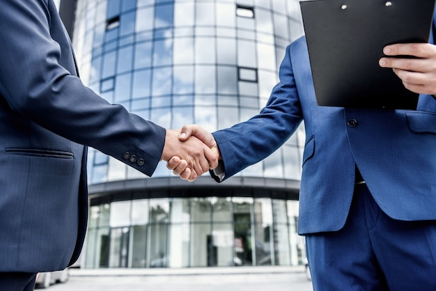 Collègues poignée de main avant immeuble de bureaux à l'extérieur close up