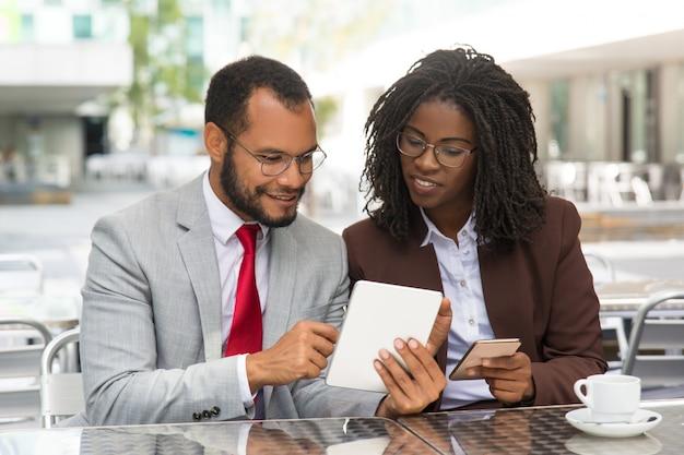 Collègues positives comparant des données sur leurs gadgets