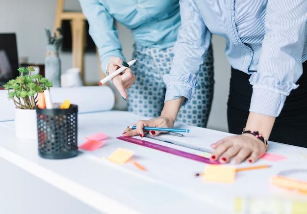 Collègues préparant un tableau avec une règle sur papier au bureau