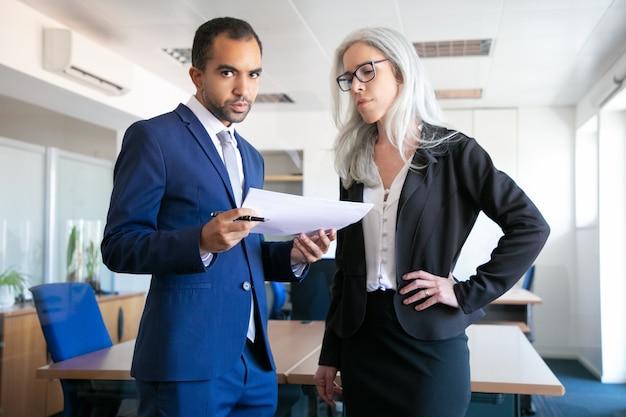Collègues professionnels debout dans la salle de réunion avec des documents. travailleuse aux cheveux gris focalisée dans le rapport de lecture de lunettes. homme d'affaires regardant la caméra. concept de travail d'équipe, d'entreprise et de gestion