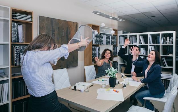 Collègues s'amusant au bureau et jetant des papiers dans une compétition de basket-ball
