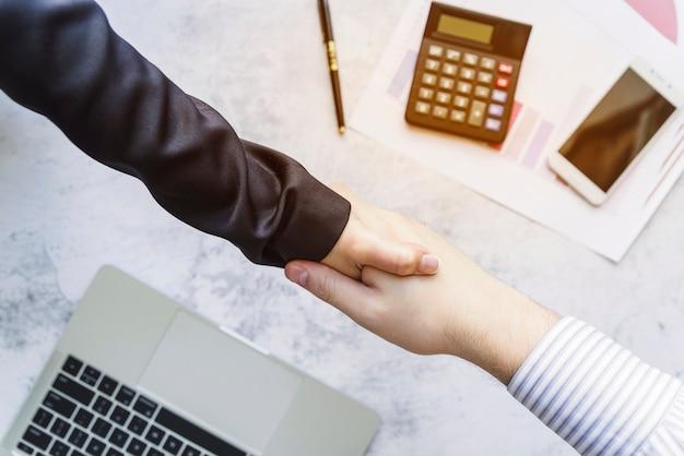 Des collègues se serrant la main au-dessus du bureau