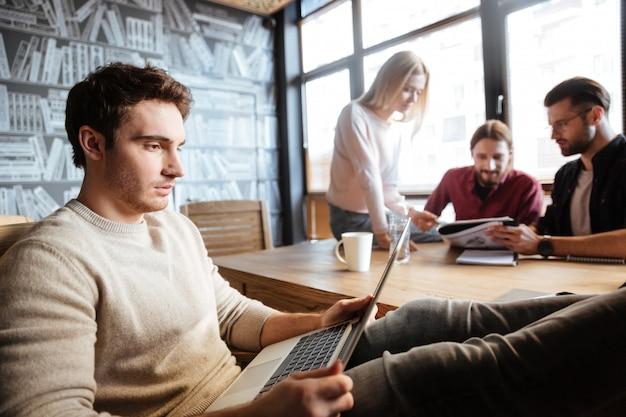 Collègues sérieux travaillant avec des documents et un ordinateur portable