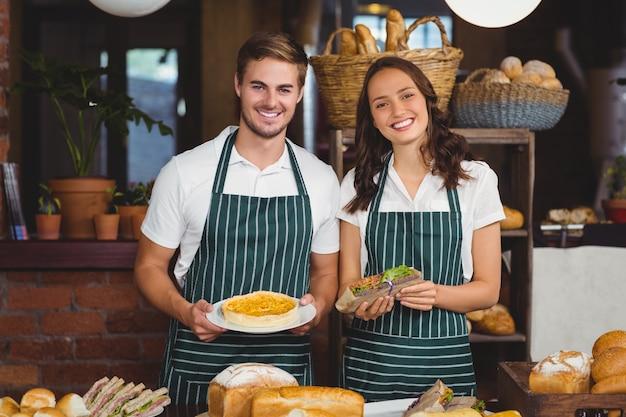 Collègues souriants montrant un sandwich et une tarte