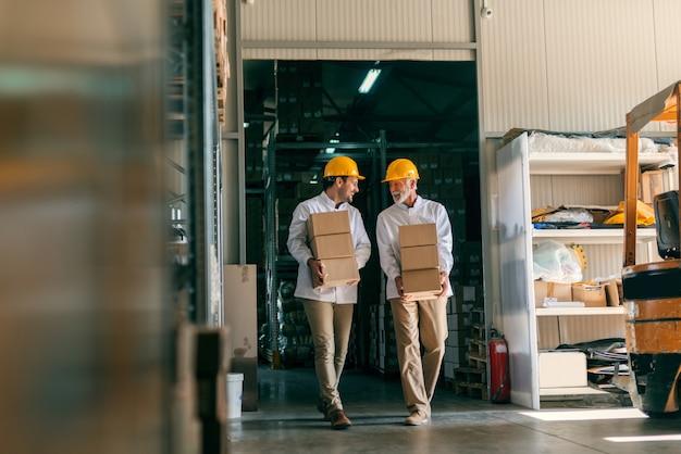 Collègues transportant des boîtes avec des casques sur la tête. intérieur de rangement.