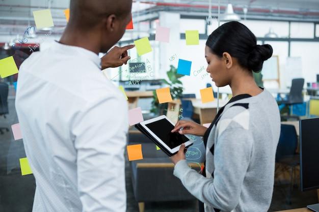 Collègues de travail à l'aide de tablette numérique tout en discutant de notes autocollantes sur verre