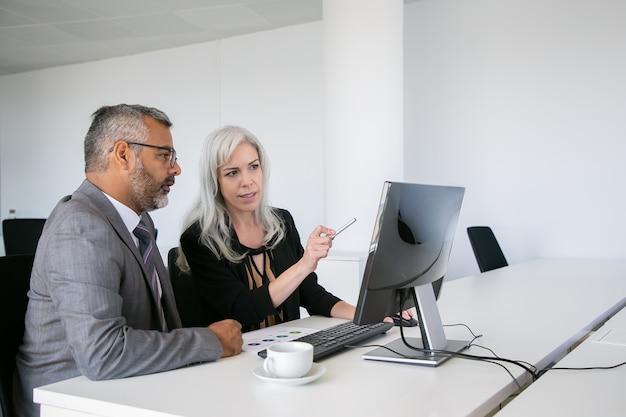 Collègues de travail ciblés regardant du contenu sur ordinateur, pointant sur l'écran et parlant assis au bureau avec un tableau papier. concept de communication d'entreprise