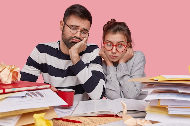 Des collègues de travail féminins et masculins tristes fatigués concentrés dans un livre, rédige un rapport, étudie la documentation, porte des lunettes transparentes, prépare un rapport