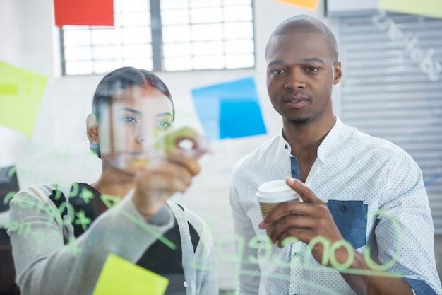 Collègues de travail lisant des notes autocollantes sur verre