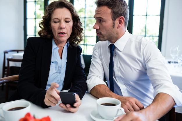 Collègues de travail à la recherche de téléphone portable tout en ayant une réunion
