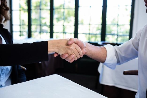 Collègues de travail se serrant la main après une réunion réussie