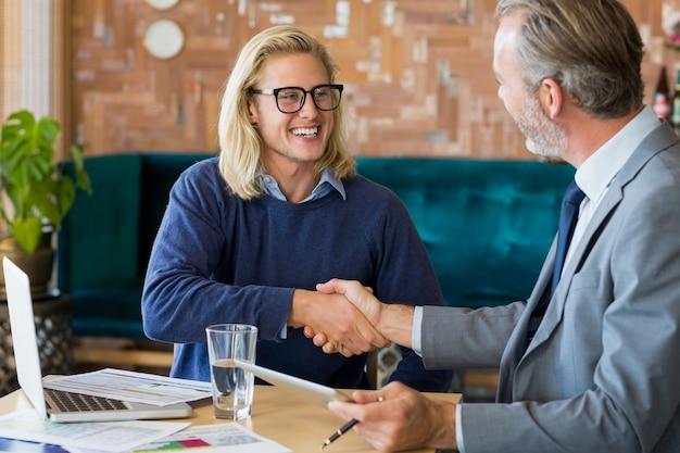 Collègues de travail se serrant la main en réunion