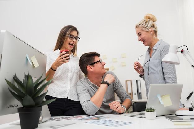 Des collègues de travail souriant et se regardant