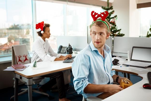 Collègues travaillant au bureau le jour de noël donnant des cadeaux.