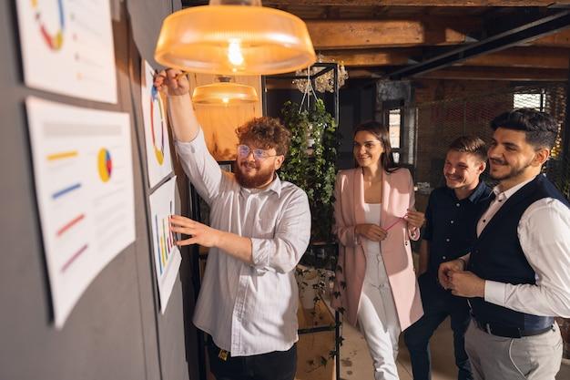 Collègues travaillant ensemble dans un bureau moderne à l'aide d'appareils et de gadgets lors d'une réunion créative