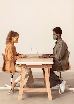 Collègues travaillant sur leurs ordinateurs portables de loin