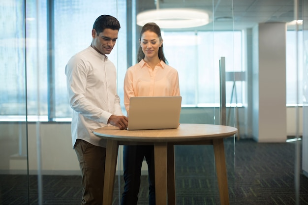 Collègues utilisant un ordinateur portable dans un bureau moderne