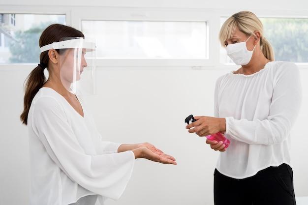 Collègues utilisant une protection faciale et un désinfectant pour les mains