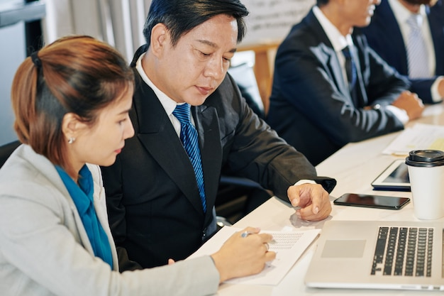 Des collègues vietnamiens discutant des données dans le rapport financier lors de la réunion