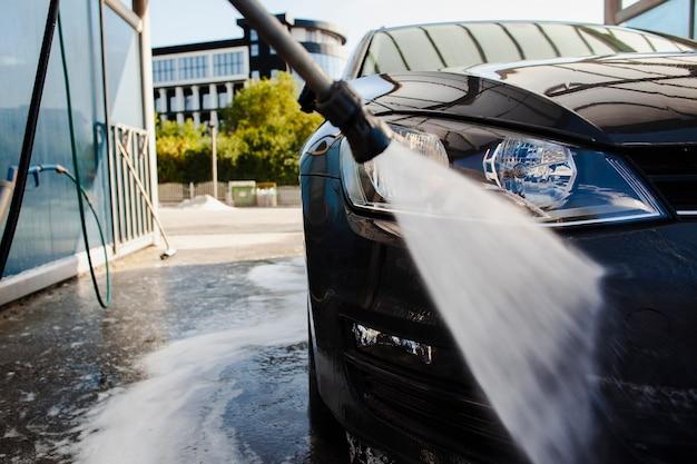 Collez le lavage devant une voiture avec de l'eau