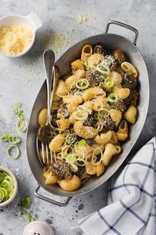 Collez pipa rigate et champignons champignon frits dans la sauce soja, avec du poivre, du parmesan et des oignons cuits à la vapeur dans un vieux bol en métal sur une vieille table vintage