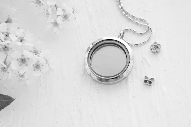 Collier en argent pour elle brillant sur blanc avec des fleurs blanches. chaînes de bijoux en argent de luxe avec verre et cristaux. petit beau cadeau en métal précieux pour femme. expressions de luxe