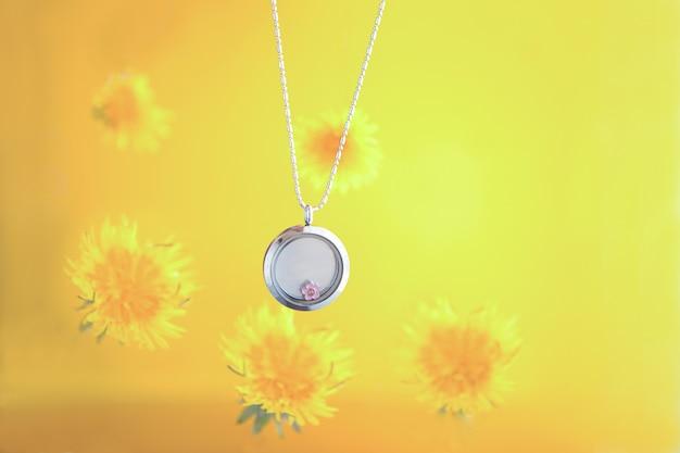 Collier en argent pour elle brillant sur fond jaune avec des pissenlits. chaînes de bijoux en argent de luxe avec verre et cristaux. petit beau cadeau en métal précieux pour femme. expressions de luxe