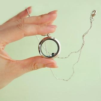 Collier en argent pour elle qui brille sur la main de la femme. chaînes de bijoux en argent de luxe avec verre et cristaux. petit beau cadeau en métal précieux pour femme. cadeau de luxe sur fond pastel