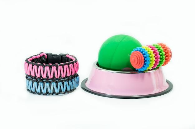 Collier, bols en acier inoxydable et jouets sur blanc isolé