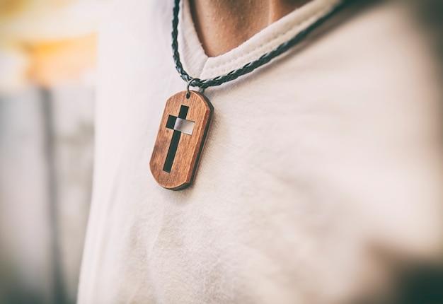Le collier croix en bois sur le cou de l'homme