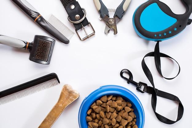 Collier, gamelle avec nourriture, laisse, friandise, peignes et brosses pour chiens. isolé sur fond blanc. vue de dessus. nature morte. espace de copie