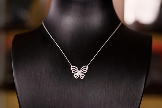 Collier en or blanc avec diamants sur un support dans une boutique de bijoux de mode. col montant noir avec bijoux de luxe, accessoires femme en vitrine.