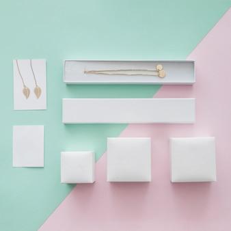 Collier en or et boucles d'oreilles avec différentes boîtes sur fond pastel