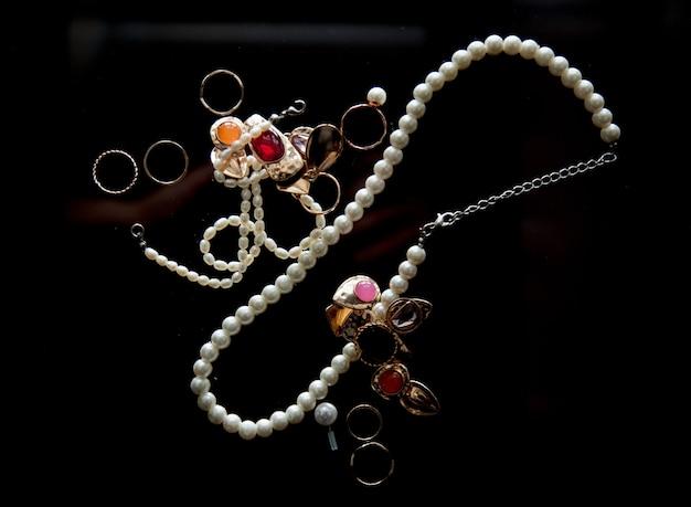 Collier avec perle et anneaux sur table en verre.