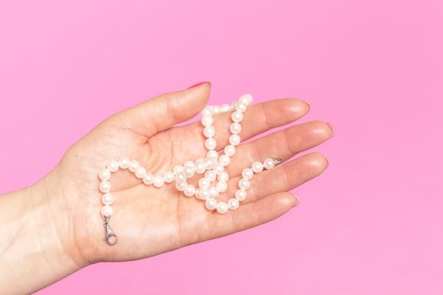 Collier de perles blanches sur la main de la femme
